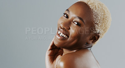 Buy stock photo Cropped shot of an attractive young woman standing with her hand on her face and smiling against a gray background