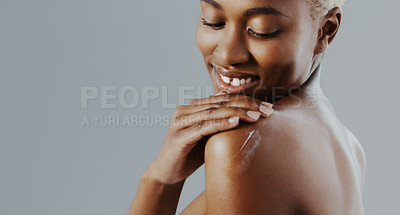 Buy stock photo Cropped shot of an attractive young woman standing alone and applying lotion to her shoulder against a gray studio background
