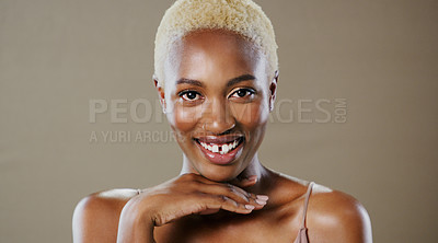 Buy stock photo Studio portrait of an attractive young woman posing and smiling while standing against a grey background