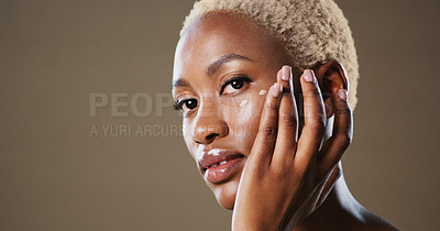 Buy stock photo Studio portrait of an attractive young woman posing and applying makeup on her face while standing against a grey background