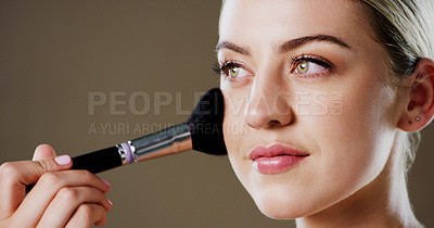 Buy stock photo Studio shot of an attractive young woman using a makeup brush on her face while standing against a grey background
