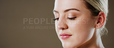 Buy stock photo Studio shot of a attractive young woman closing her eyes while standing against a grey background