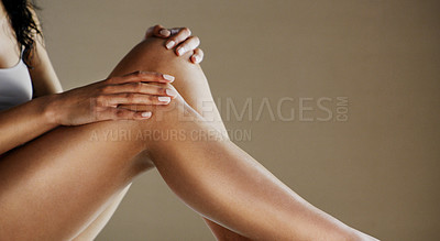 Buy stock photo Studio shot of an unrecognizable woman holding her exposed legs while being seated on the ground against a grey background