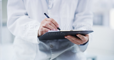Buy stock photo Closeup shot of a scientist writing notes on a clipboard in a lab