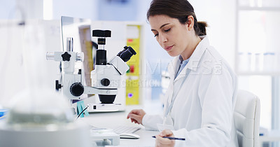 Buy stock photo Shot of a young scientist writing notes while using a microscope in a lab