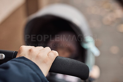 Buy stock photo Cropped shot of unrecognizable father pushing his infant daughter in her stroller outdoors