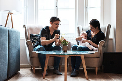 Buy stock photo Shot of a happy young couple feeding and spending time with their infant daughter at home