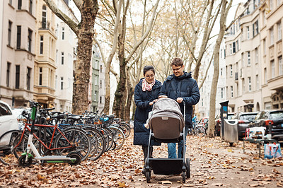 Buy stock photo Full length shot of a young couple pushing their infant daughter in her pram on a day spent together outdoors