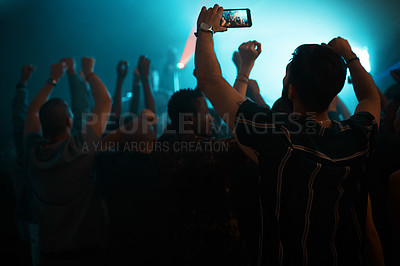 Buy stock photo Rearview shot of an unrecognizable man holding up a camera phone while standing in the crowd in a nightclub