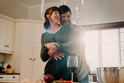 Buy stock photo Shot of a woman cooking while being embraced by her husband at home