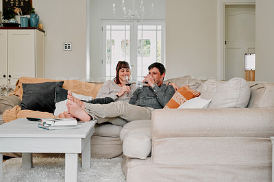 Buy stock photo Shot of a couple having wine while relaxing on the sofa at home