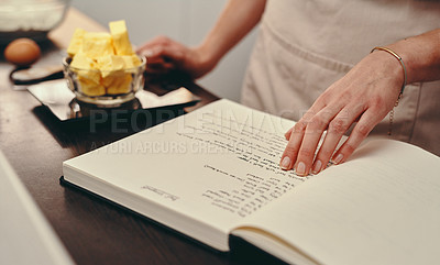 Buy stock photo Cropped shot of an unrecognizable woman reading a recipe from a book while baking at home