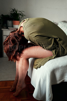 Buy stock photo Cropped shot of a young woman suffering from stomach pains inside her bedroom at home
