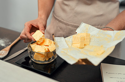 Buy stock photo Cropped shot of an unrecognizable woman adding blocks of butter inside a bowl while baking inside her kitchen at home