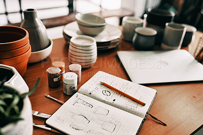 Buy stock photo Cropped shot of a potter's sketches in a notebook on a work desk in her workshop