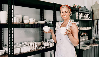 Buy stock photo Cropped portrait of an attractive mature woman standing and organising her pottery on a shelf in her workshop