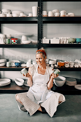 Buy stock photo Full length portrait of an attractive mature woman sitting on the floor and holding her pottery in her workshop