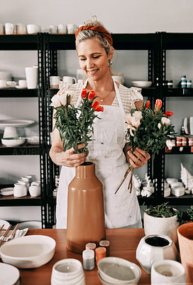 Buy stock photo Cropped shot of an attractive mature woman standing alone and putting flowers into a handmade vase in her pottery workshop