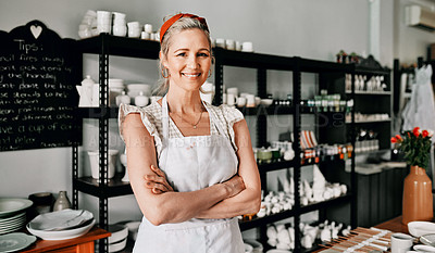 Buy stock photo Cropped portrait of an attractive mature woman standing with her arms folded in her pottery workshop