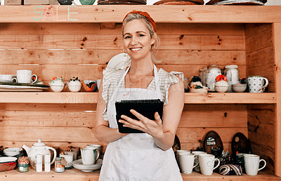 Buy stock photo Cropped portrait of an attractive mature woman standing alone and using a tablet in her pottery workshop