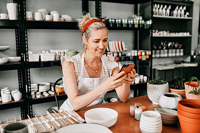 Buy stock photo Cropped shot of an attractive mature woman sitting alone and using her cellphone in her pottery workshop