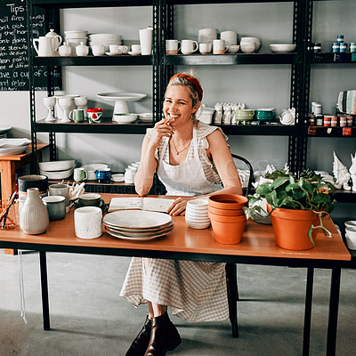 Buy stock photo Cropped portrait of an attractive mature woman sitting alone at her desk in her pottery workshop