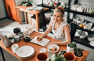 Buy stock photo High angle portrait of an attractive mature woman sitting alone in her pottery workshop and sketching in a notebook