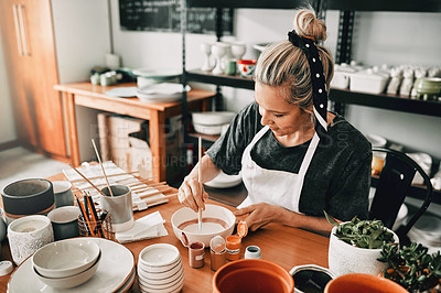 Buy stock photo Cropped shot of an attractive mature woman sitting alone and painting a pottery bowl in her studio