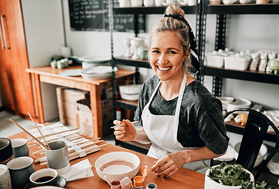 Buy stock photo Cropped portrait of an attractive mature woman sitting alone and painting a pottery bowl in her studio