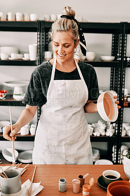Buy stock photo Cropped shot of an attractive mature woman standing alone and painting a pottery bowl in her workshop