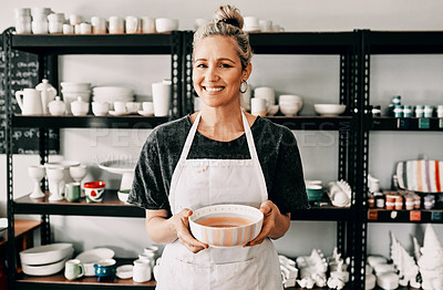 Buy stock photo Cropped portrait of an attractive mature woman standing alone and holding her finished pottery in her workshop
