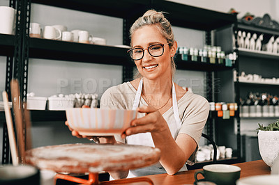 Buy stock photo Cropped shot of an attractive mature woman sitting alone and admiring her finished pottery in her workshop