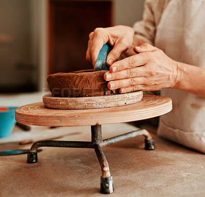 Buy stock photo Cropped shot of an unrecognizable woman shaping a clay pot in her workshop