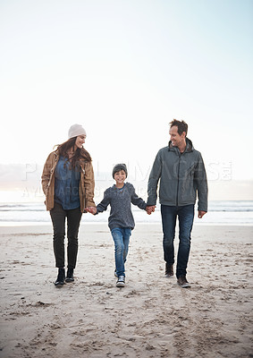 Buy stock photo Full length portrait of a happy young family holding hands and walking along the beach together during a day out