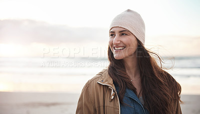 Buy stock photo Cropped shot of an attractive young woman standing alone and smiling during a day out on the beach