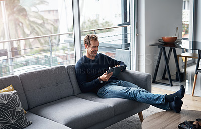 Buy stock photo Full length shot of a handsome young man sitting alone on the sofa at home and using a tablet