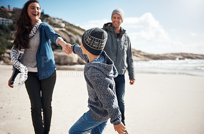 Buy stock photo Cropped shot of a happy young boy feeling playful and pulling his mother during a day out on the beach