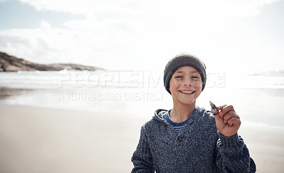 Buy stock photo Cropped portrait of a happy young boy standing and holding up a seashell while spending the day on the beach
