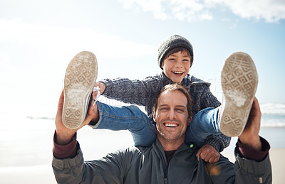 Buy stock photo Cropped portrait of a handsome young man feeling playful while carrying his son on his shoulders at the beach