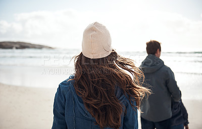 Buy stock photo Rearview shot of an unrecognizable woman walking along the beach with her family during a day out