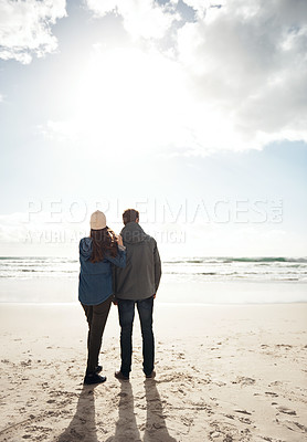 Buy stock photo Full length shot of an unrecognizable woman standing with her husband during a day out on the beach