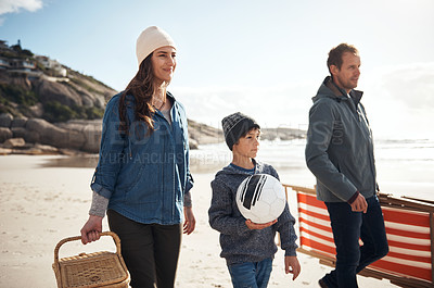 Buy stock photo Cropped shot of a happy young family walking along the beach for a picnic during a day out