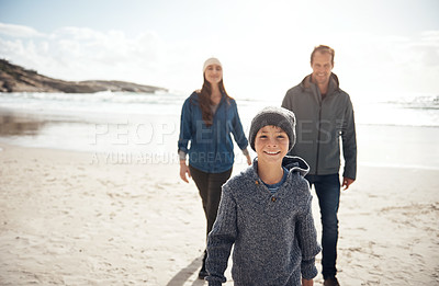 Buy stock photo Cropped portrait of a happy young family walking along the beach together during a day out