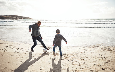 Buy stock photo Full length shot of a happy young boy playing soccer on the beach with his father during a day out