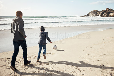 Buy stock photo Full length shot of a young boy playing soccer on the beach with his father during a day out