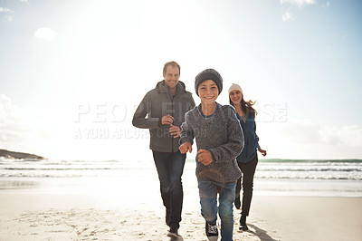 Buy stock photo Cropped portrait of a happy young family playfully running along the beach together during a day out