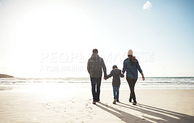 Buy stock photo Full length shot of an unrecognizable family holding hands and walking along the beach together during a day out
