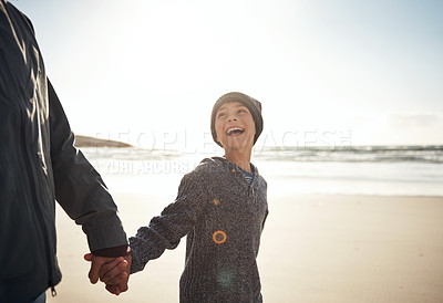 Buy stock photo Cropped shot of a happy young boy standing and holding his father's hand during a day out on the beach