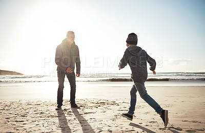 Buy stock photo Full length shot of a happy young boy running to his father during a day out on the beach
