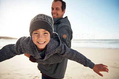 Buy stock photo Cropped portrait of a handsome young man feeling playful and carrying his son during a day out on the beach